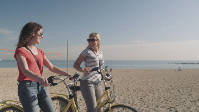 stockvideo's en b-roll-footage met young adult tourist cycling on beach in summer - duurzaam toerisme
