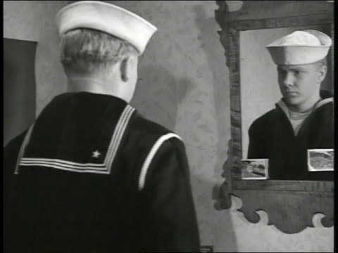 vidéos et rushes de young adult us navy sailor putting on cap in front of mirror saluting 'aye aye sir' ws soldiers in uniform piling duffel bags in stack at train... - marin