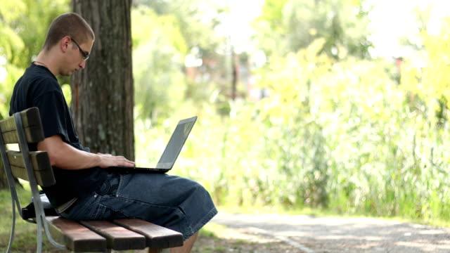 junger erwachsener mit laptop im öffentlichen park - nur junge männer stock-videos und b-roll-filmmaterial