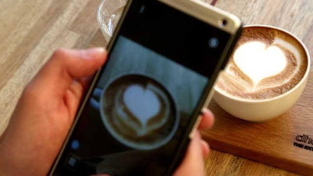 young adult using smart phone for capture his coffee - photographing stock videos and b-roll footage
