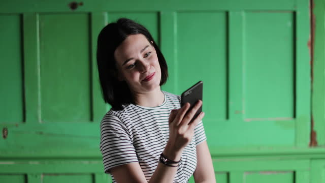 young adult using smartphone with green wall background - リサイクル素材点の映像素材/bロール