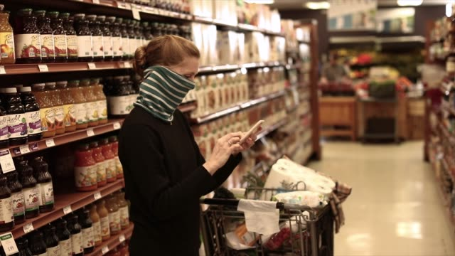 young adult wearing cloth face mask in market aisle checks i phone - supermarkt einkäufe stock-videos und b-roll-filmmaterial