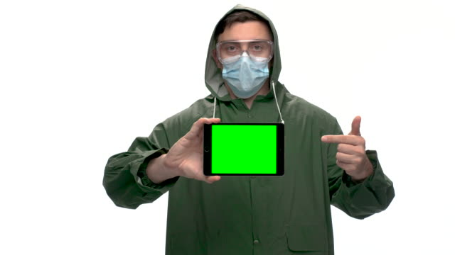 young adult with green raincoat holding digital tablet with chroma key green screen - raincoat stock videos & royalty-free footage