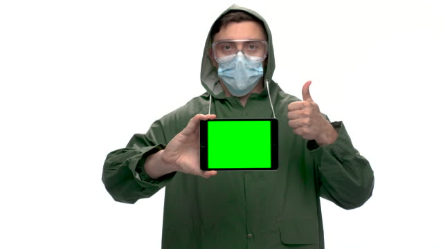 young adult with green raincoat holding digital tablet with chroma key green screen, slow motion - raincoat stock videos & royalty-free footage