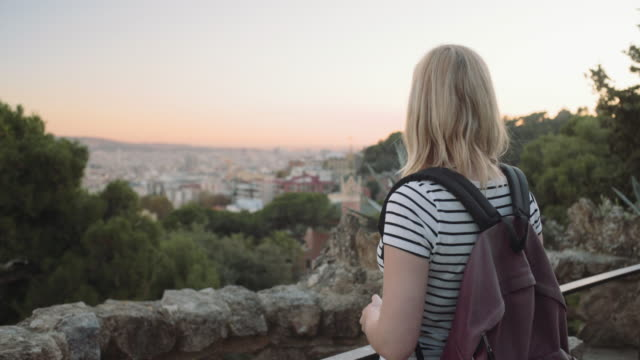 young adult woman admiring view backpack in park barcelona - バックパック点の映像素材/bロール