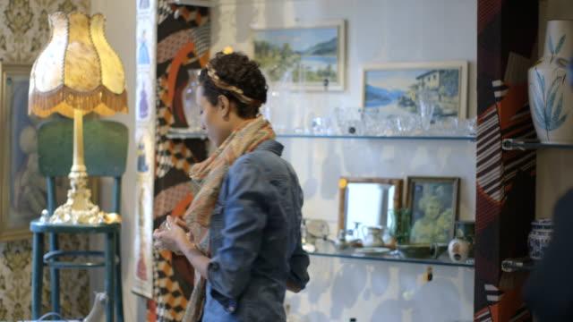vidéos et rushes de jeune adulte femme navigation dans une deuxième main store - miroir ancien