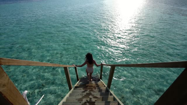 young adult woman chasing the sun in maldives - steps stock videos & royalty-free footage