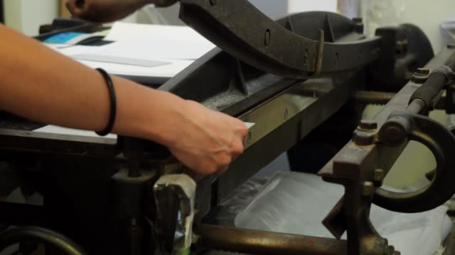 Young adult woman cutting paper to make a copybook