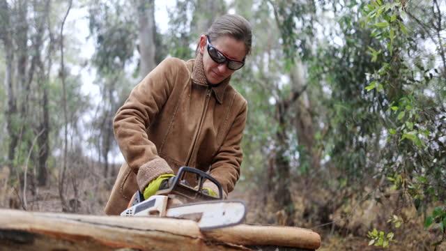 チェーンソーで木を切る若い大人の女性 - 木材産業点の映像素材/bロール