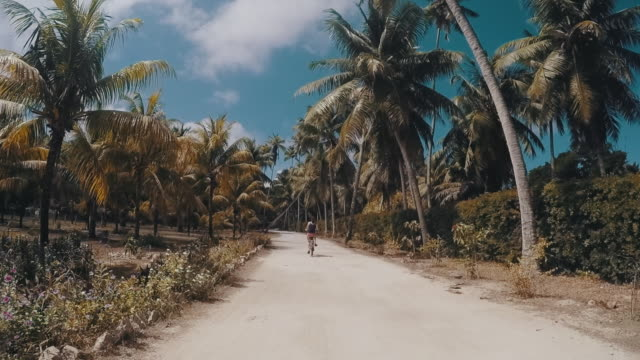 Young adult woman cycling in Seychelles