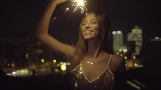 young adult woman dancing on rooftop with sparkler - sequin stock videos & royalty-free footage