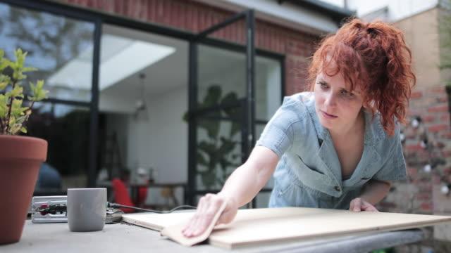 vídeos y material grabado en eventos de stock de young adult woman doing carpentry diy in garden - reforma