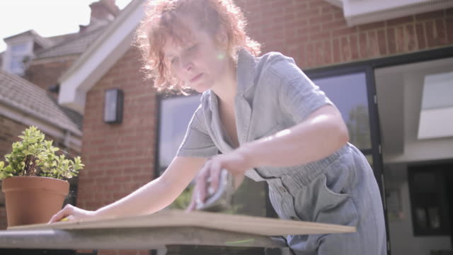 young adult woman doing carpentry diy on patio - patio stock videos & royalty-free footage