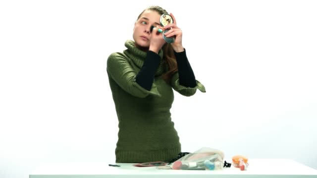 Young adult woman doing her make-up