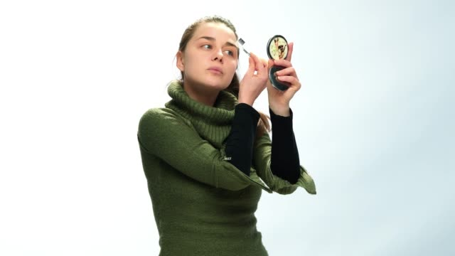 Young adult woman doing her make-up white background