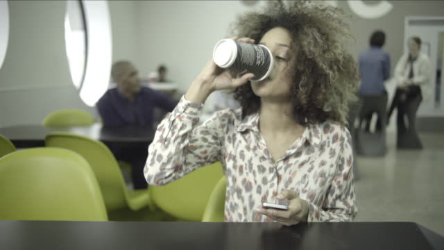 young adult woman drinking coffee in café - disposable cup stock videos and b-roll footage