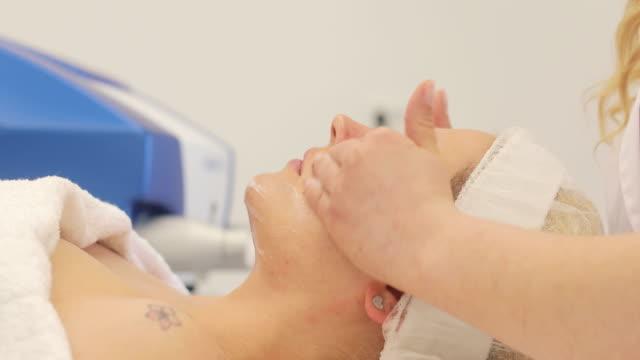 vídeos de stock e filmes b-roll de young adult woman enjoying beauty treatment at dermatologist - casca de fruta