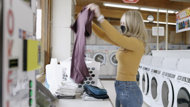 young adult woman folding laundry at laundromat - rules stock videos & royalty-free footage