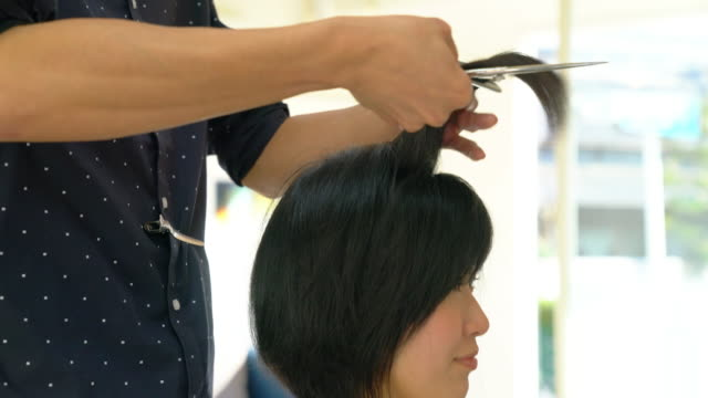 young adult woman getting her hair cut and styled at a salon - hairdresser stock videos & royalty-free footage