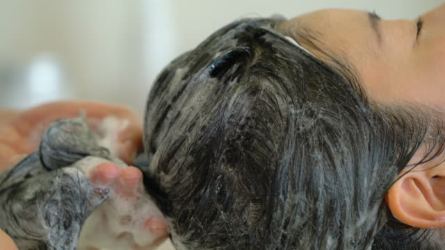 young adult woman getting her hair washed at a hair salon - shampoo per capelli video stock e b–roll