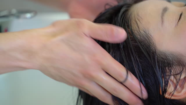 young adult woman getting her hair washed at a hair salon - beauty salon stock videos and b-roll footage