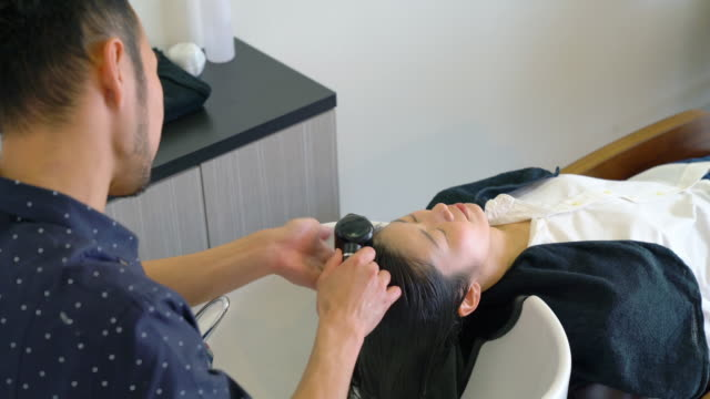 Young adult woman getting her hair washed at a hair salon