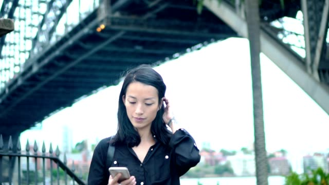 young adult woman have a break and typing something on smart phone next to sydney harbour bridge - white collar worker stock videos and b-roll footage