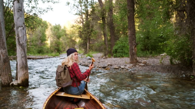 young adult woman in a canoe on a wilderness river - kayak video stock e b–roll