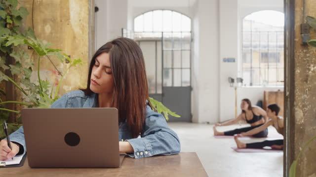 junge erwachsene frau arbeitet mit einem laptop in einem multifunktionalen raum, während andere menschen im hintergrund trainieren - generation z stock-videos und b-roll-filmmaterial
