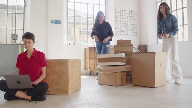 若い大人の女性は、新しいロフトオフィスで彼女のラップトップで作業しています - 1日目点の映像素材/bロール