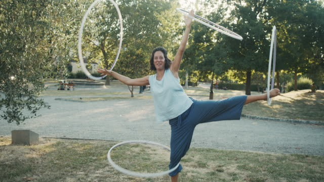 young adult woman juggling with hula hoop at the public park - juggling stock videos & royalty-free footage