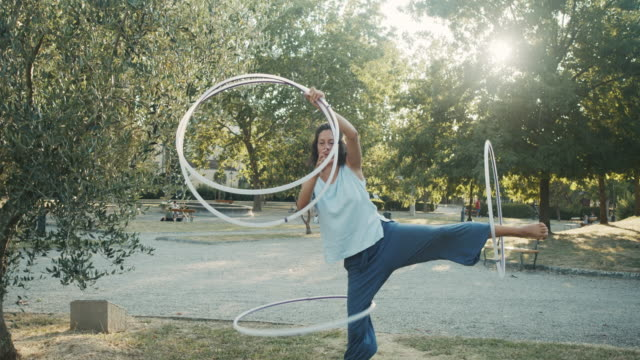 young adult woman juggling with hula hoop at the public park - plastic hoop stock videos & royalty-free footage