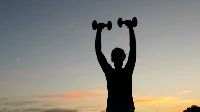 young adult woman lifting weights outdoors after sunset - continuity stock videos and b-roll footage