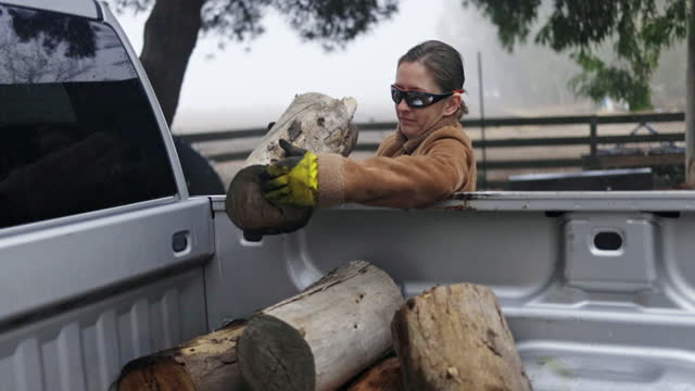 vídeos y material grabado en eventos de stock de mujer adulta joven cargando madera en un camión - leñador