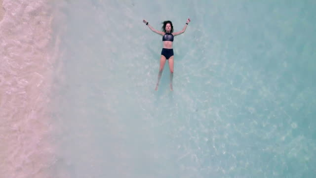young adult woman lying down on a paradisiac turquoise water in maldives - island stock videos & royalty-free footage