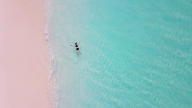 young adult woman lying down on a paradisiac turquoise water in maldives - turquoise colored stock videos & royalty-free footage
