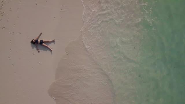 vídeos y material grabado en eventos de stock de mujer adulta joven tumbada en una playa paradisíaca contra el agua turquesa en maldivas - el cielo