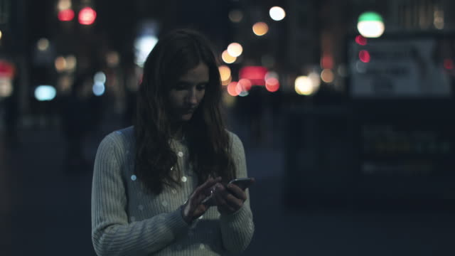 vidéos et rushes de young adult woman on mobile in new york - droit