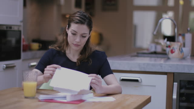 young adult woman opening bills at home - letter document stock videos and b-roll footage
