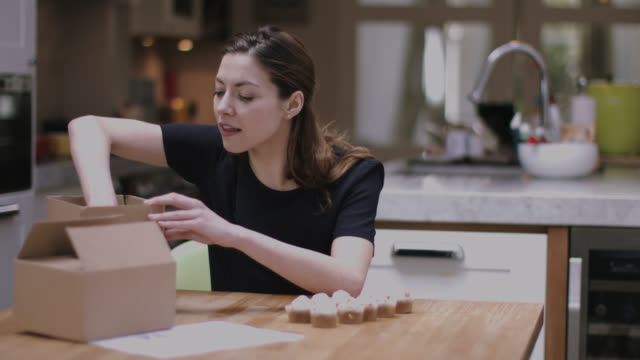 Young adult woman packing cupcakes at home