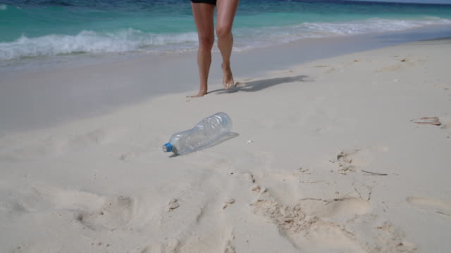 young adult woman picking up some abandoned plastic bottles on the beach - raccogliere frutta video stock e b–roll