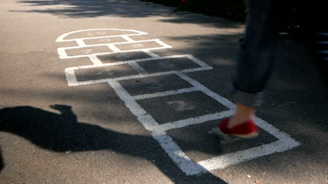 Young adult woman playing hopscotch outdoors