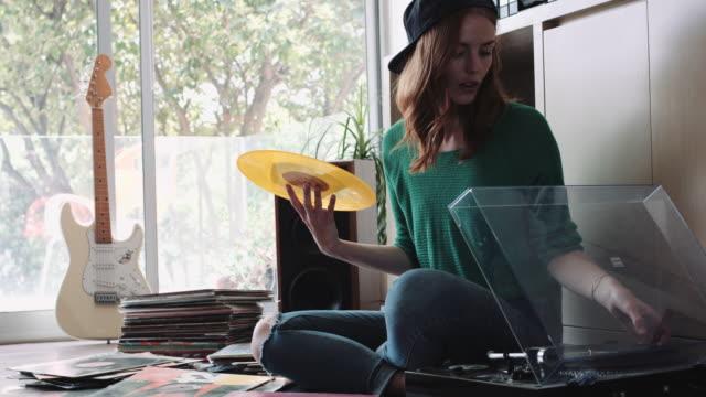 vídeos y material grabado en eventos de stock de young adult woman playing vinyl records at home - gorra de béisbol
