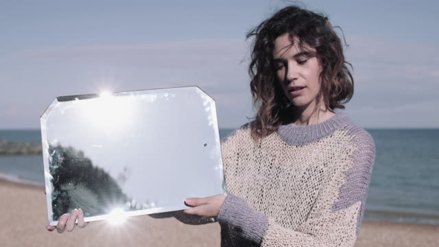 young adult woman reflecting mirror by the sea. - spiegel stock-videos und b-roll-filmmaterial