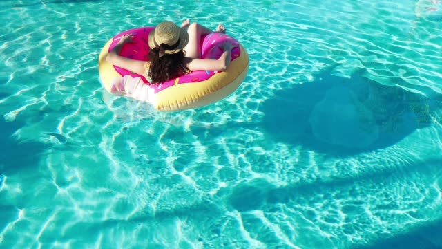 Young adult woman relaxing herself floating on water