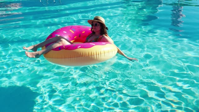young adult woman relaxing herself floating on water - floating on water stock videos & royalty-free footage