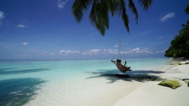 junge frau auf einer schaukel in einem tropischen paradies - malediven stock-videos und b-roll-filmmaterial