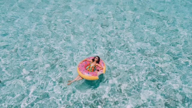 vídeos de stock e filmes b-roll de young adult woman relaxing on inflatable in the sea - comida doce