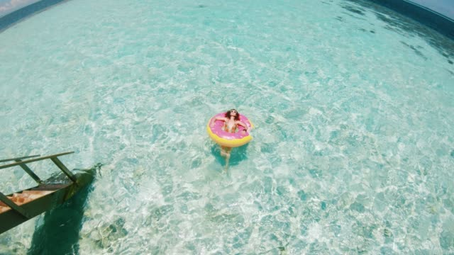 young adult woman relaxing on inflatable in the sea - doughnut stock videos and b-roll footage