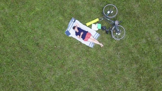 vídeos de stock, filmes e b-roll de adulta jovem, descansando em um parque público - vista aérea - domingo